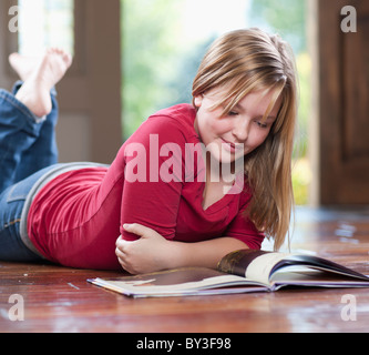 USA, Utah, Girl (10-11) reading book in home Banque D'Images