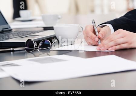 Mains de businesswoman écrit quelque chose sur le papier avec l'ordinateur portable, tasse, stylo et documents près de par