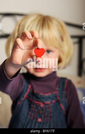 Stock photo d'une fille de cinq ans qui fait une forme de coeur rouge dans sa main.