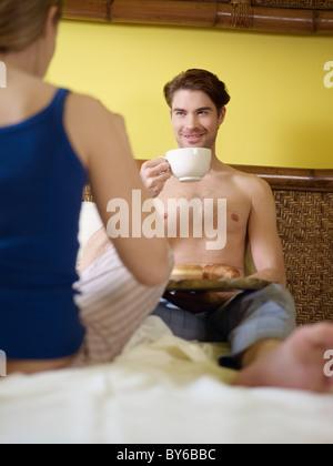 Young heterosexual couple eating croissant et de boire du café au lit. La forme verticale, vue arrière, se concentrer Banque D'Images