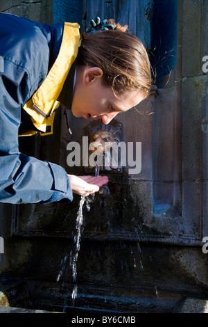 Femme boit à Saint Anne's (St Anne 's / Ann's / Ann) et puits d'eau minérale / guérison / avec les eaux de source. Banque D'Images