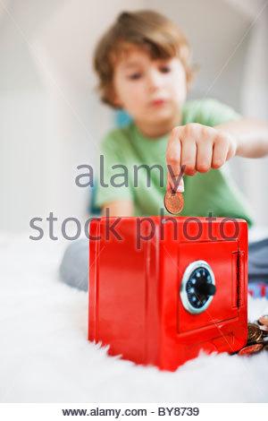 Boy putting coins en safe piggy bank Banque D'Images