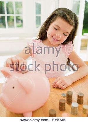 Girl putting coins en piggy bank Banque D'Images
