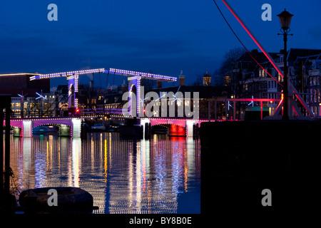 Le Magere Brug ou Skinny Bridge Amsterdam est un célèbre monument. Sur la rivière Amstel au crépuscule en hiver Banque D'Images