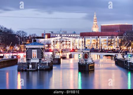 Amsterdam Amstel avec Skinny Bridge, Magere Brug et Muziektheater, de l'Opéra au crépuscule en hiver. Banque D'Images