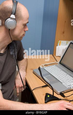Un jeune adulte homme avec écouteurs, parle dans un microphone connecté à son ordinateur portable lors d'un entretien. Banque D'Images