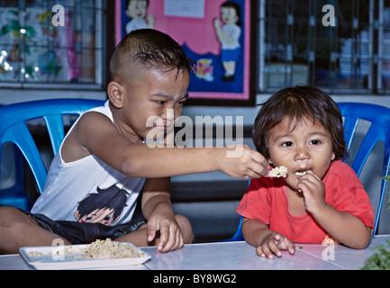 Scène humoristique d'un jeune garçon d'essayer de nourrir sa petite sœur. S. E. Asie Thaïlande Banque D'Images