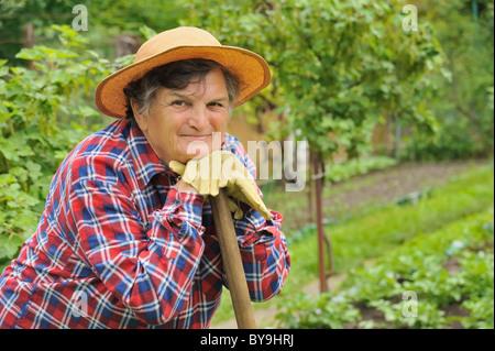 Senior woman gardening - reposant sur ses hoe après le travail Banque D'Images