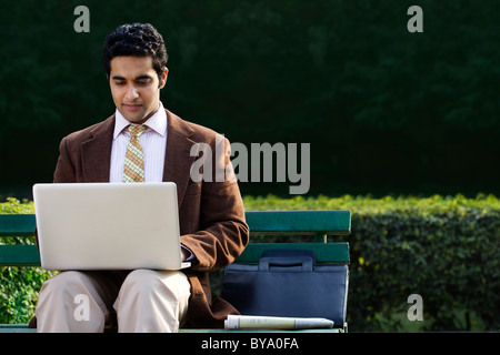 Businessman working on a laptop in a park Banque D'Images