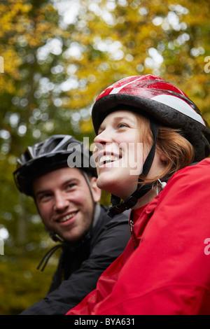 Couple du vélo à travers les arbres Banque D'Images
