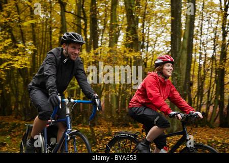 Vélo Couple entouré d'arbres Banque D'Images