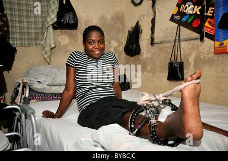 Jeune femme blessés dans le tremblement de terre de janvier 2010 assis sur le lit dans sa maison dans les bidonvilles Banque D'Images