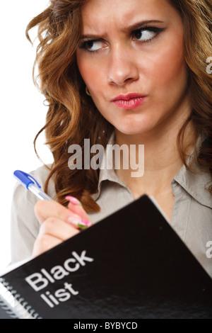 Angry woman noms dans un ordinateur portable 'liste noire' Banque D'Images