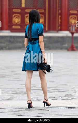 Jeune femme chinoise élégante en robe bleue avec appareil photo reflex numérique Canon holding gun flash dans le Banque D'Images