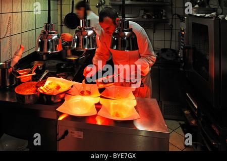 Chef de la préparation d'un menu dans un restaurant de cuisine, plaques d'être réchauffé à la chaleur des lampes, Banque D'Images