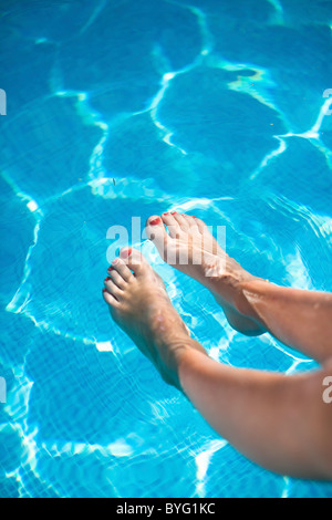 Pieds de womans in swimming pool Banque D'Images