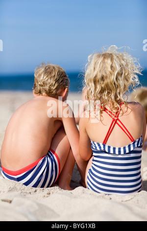 Des enfants assis sur la plage Banque D'Images