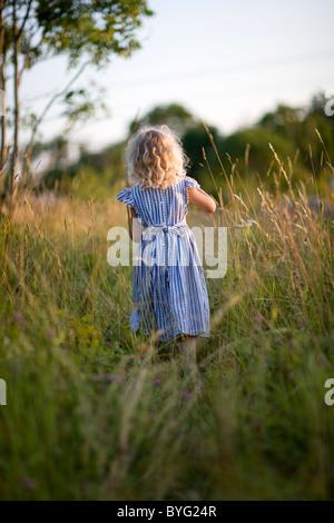 Girl standing on meadow, vue arrière