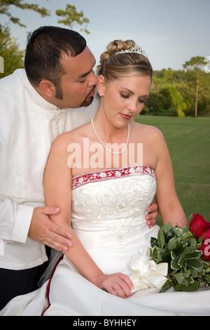 Mariée et le marié romantique partager une tendre étreinte sur l'herbe pendant une pause à la réception. Banque D'Images