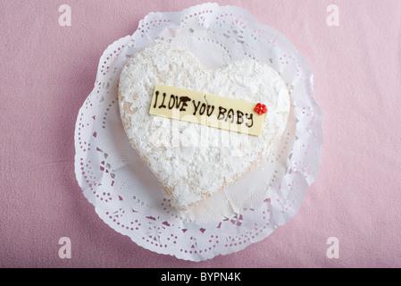 """Pâtisserie en forme de coeur avec lettrage décoratif sur le chocolat blanc la lecture, """"I love you baby' Banque D'Images"""