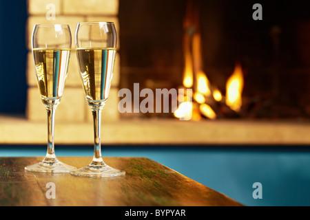 Libre de deux verres à vin avec du champagne sur la table et cheminée en arrière-plan. La forme horizontale