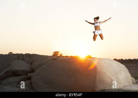 Une femme saute de joie sur à d'un rocher surplombant un lac Banque D'Images