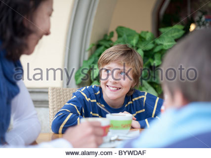 Boy talking to woman at cafe table Banque D'Images