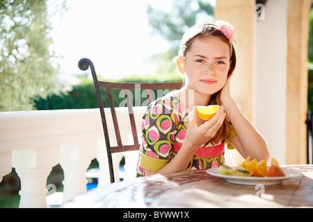Girl eating oranges fraîches Banque D'Images