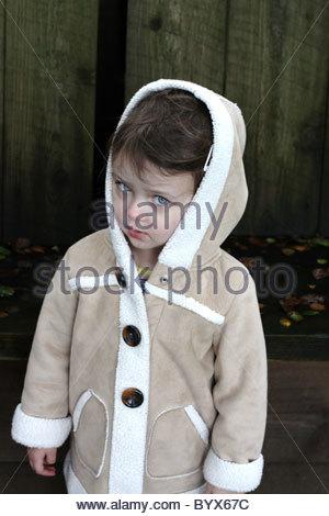 Une fillette de 3 ans dans un manteau. Banque D'Images