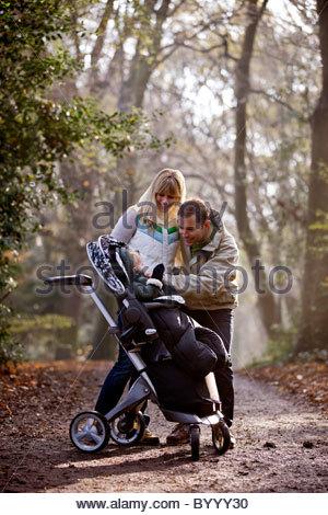 Un jeune couple souriant à leur fils dans une poussette Banque D'Images