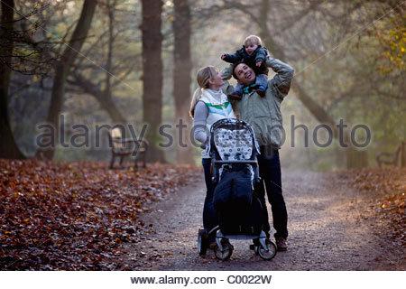 Un comité permanent de la famille dans le parc, le père portant son fils sur ses épaules Banque D'Images
