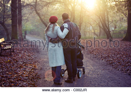 Un jeune couple en poussant une poussette dans le parc, vue arrière Banque D'Images