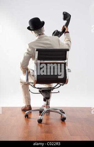 Homme assis avec récepteur téléphone géant a tenu à l'écart de l'oreille Banque D'Images