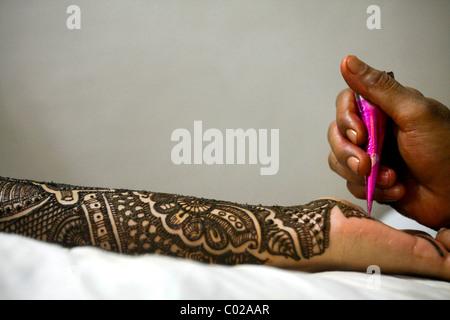 Une Indienne mariée obtient sa main et bras peint au henné. Banque D'Images