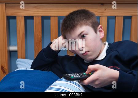 Un modèle photo parution d'un garçon de onze ans regardant la télévision dans sa chambre au Royaume-Uni Banque D'Images