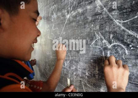 Un garçon étudiant est un dessin d'un animal sur un tableau, à un aperçu de l'école primaire en milieu rural au Banque D'Images