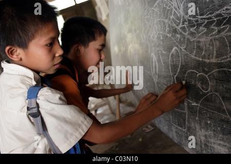 Un groupe de garçons sont des dessins sur un tableau, à un aperçu de l'école primaire en Laos communiste. Banque D'Images