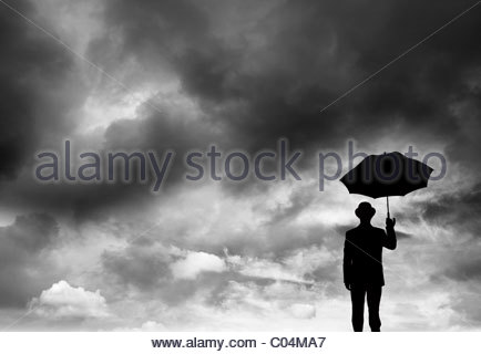 Businessman holding an umbrella dans une tempête Banque D'Images
