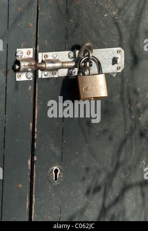 Un cadenas en laiton sur un hangar porte. Des cadenas sont utiles pour dissuader les voleurs occasionnels. Banque D'Images