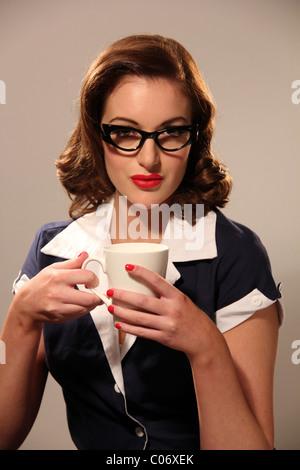 Femme en robe de style années 50, tenant une tasse Banque D'Images