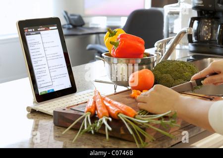 La cuisine femme dans la cuisine tout en suivant les instructions de cuisson sur un iPad en ligne Banque D'Images