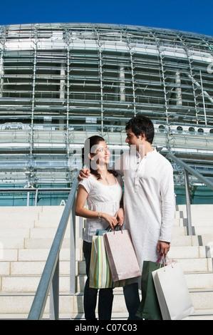 Couple debout sur l'escalier d'un centre commercial Banque D'Images