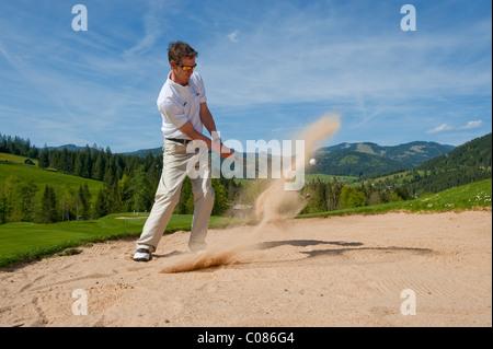 Joueur de golf debout dans le bunker de la boule de golf au bâton du sable, sur le terrain de golf alpin, Achenkirch, Banque D'Images