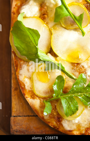 Et mince croûte croustillante Pizza à la Mozzarella, fromage de chèvre, Fig Propagation, poire et roquette préparé Banque D'Images