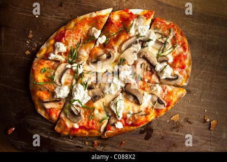 Et mince croûte croustillante Pizza à la Mozzarella, champignons, fromage de chèvre et basilic préparé par Gianni Banque D'Images