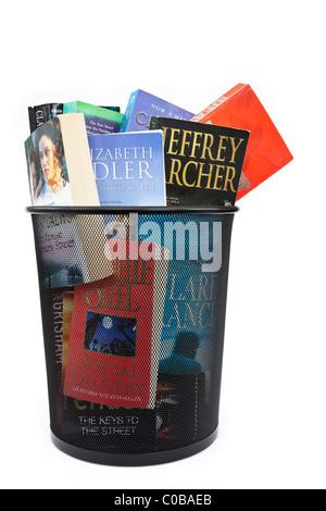 Des livres de poche jeté dans une corbeille à papier bin pour illustrer l'évolution des habitudes de lecture concept. Banque D'Images