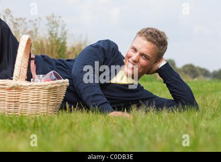 Beau jeune blond couché dans l'herbe avec panier pique-nique Banque D'Images