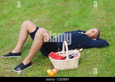 Jeune garçon blond allongé sur l'herbe avec panier pique-nique Banque D'Images