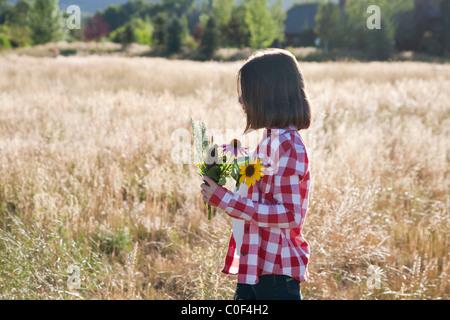 Girl holding un bouquet de fleurs sauvages dans la zone