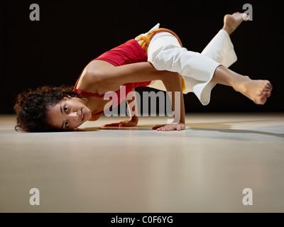 Portrait de jeune adulte femme latino-américaine faisant du yoga et de capoeira au gymnase. Banque D'Images